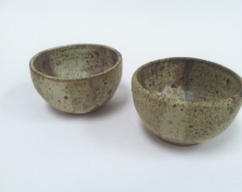 Thick speckled tea bowls, painted with abstract designs