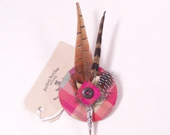 A tartan and feather brooch