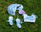 Little boy blue layette set features hat, booties, and bib with paw prints