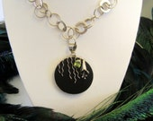 Gentle rain falls on silver flower and faceted green gem necklace