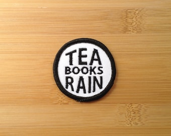 "Tea Books Rain Patch - Iron or Sew On - 2"" - Embroidered Circle Appliqué - Black White - Cozy Nerd Phrase - Hat Bag Accessory Handmade USA"
