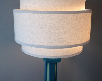 3 Tiered hardback lamp shade in off-white muslin fabric with edge trimming, best for floor lamps. Free shipping to lower 48 states.