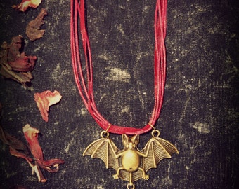 Vampires Kiss - SUMMER SALE!!! Blood red 'ruby' gem drop dangles from a creepy vampire bat. Size adjustable organza mix cord.