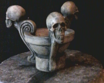 Solid cast cement stone-colored skull candle holder durable, and heat-proof.