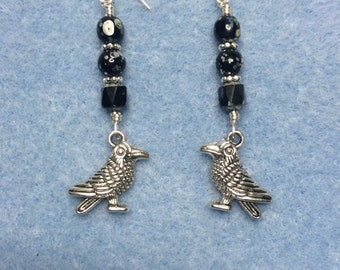 Silver raven charm dangle earrings adorned with black Czech glass beads.