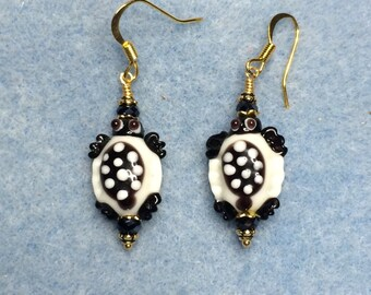 Black and white spotted lampwork turtle bead earrings adorned with black Chinese crystal beads.