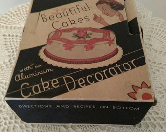 Vintage beautiful cake aluminum cake decorator. 1940s -1950s. In original box with six tips in nice condition. Box has wear.