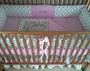 Pink and gray baby bed set with triple ruffled skirt.