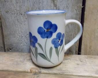 Vintage mug with floral paintings.