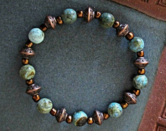 Larimar bead bracelet, with metallic and glass beads, on stretch jewelry fiber.