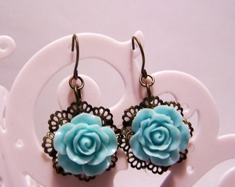antiqued brass earrings with light blue resin flower on filigree