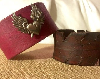 Magenta leather bracelet with a metal hart with wings.