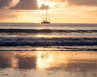 Sailboat at golden sunrise with reflection