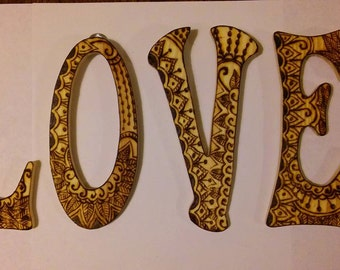 Love word art. Henna wall hanging letter. Pyrography.
