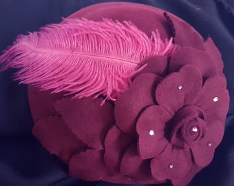 Fascinator wool hat with rhinestone embellishment on flower, accented with feathers. Red or burgundy.