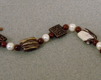 Handmade beaded bracelet of peanut agate, mahogany obsidian, and pearls with filigree copper beads