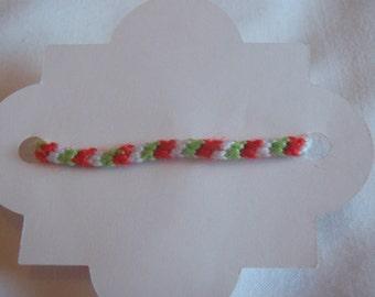 Diagonal friendship bracelet. (White, green and red.)