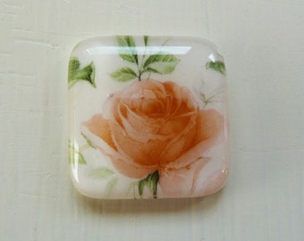Fused glass cabochon with pink, green, and peachy orange floral rose design.