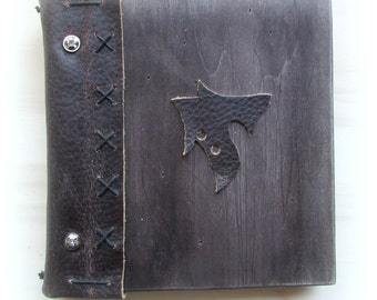 Book of wood bound in leather with leather cover motif