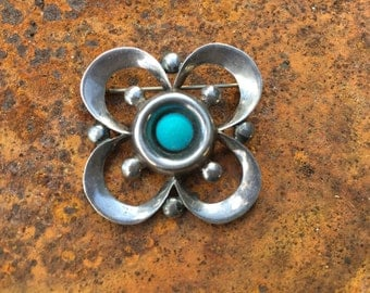 Mexican sterling brooch with turquoise cabochon center