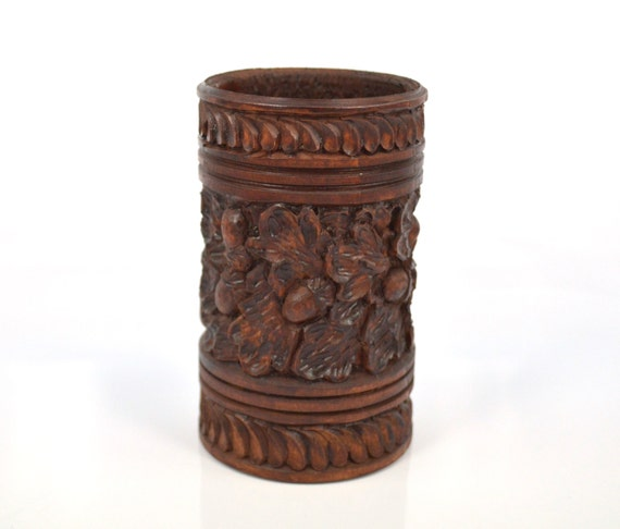 Carved wooden pencil and pen holder with a pattern in the form