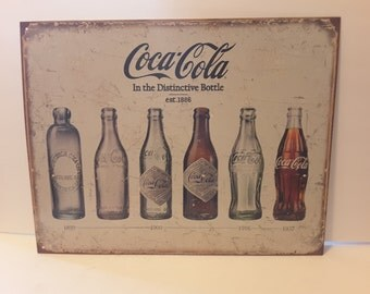 Coke tin showing vintage bottles