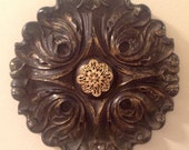 Medallion wall decor plaque, black and gold round with gold jewelry detail