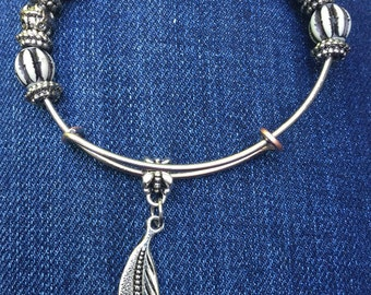 Adjustable beaded bangle charm bracelet. Feather charm.