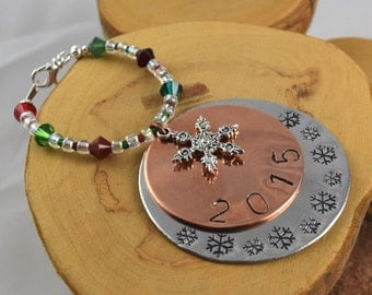 Round layered aluminum and copper hand stamped 2015 ornament featuring Swarovski crystals and a snowflake charm too