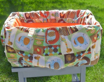 Shopping cart cover for babies or toddlers. Orange with animals.