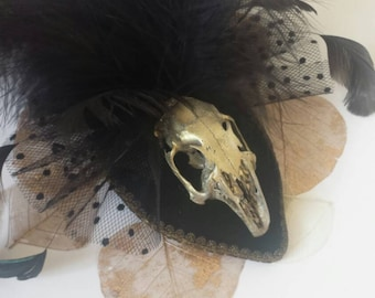 Rabbit skull head piece fascinator. Gold and green with feathers and gold trim.