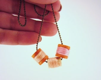 Itty bitty spool charm necklace. Shades of hombre pink. Bronze ball chain. Perfect gift for sewer, seamstress.