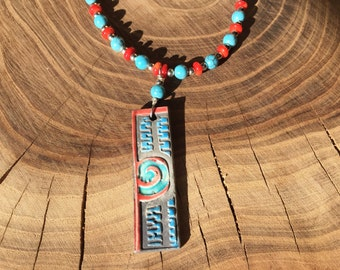 Hand carved raku pendant with necklaces beaded in coral and turquoise.