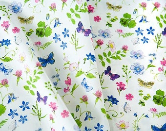 Organic cotton fabric printed with spring flowers, butterflies in pink, blue, purple, green. Certified organic Cotton by 1/2 meter or yard.