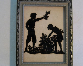 framed antique cut paper silhouette of children in a garden