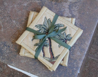 TAPESTRY PALM TREE Coasters with faux Dupioni Silk bindings. Approx 4 1/2 inches square in tan green brown. Set of four