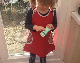Lovely Girls' 'Shangri La', red pinafore dress, white edging, liberty print circular pockets, vintage / retro / 60s style