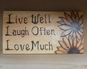 Live Well, Laugh often Love much sign with sunflowers on knotty pine