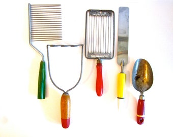 Vintage kitchen tools, collection of chipped wood, bakelite and metal masher, slicer, scoop and cheese slicer