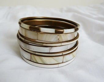Seven vintage brass, mother of pearl and white enamel bangles