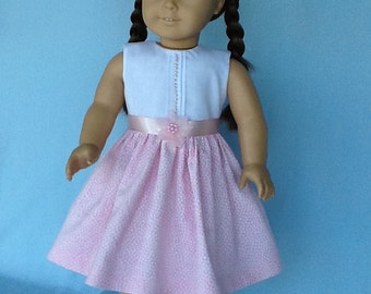 Fits American Girl Doll and other 18 inch dolls.  Sleeveless pink and white dress and hair clip..