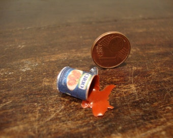 miniature cans tomato sauce, open and overturned