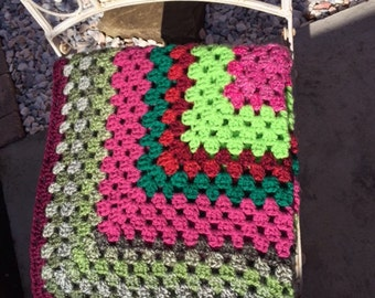 Beautiful crocheted baby blanket in fluffy soft greens, pinks, purples