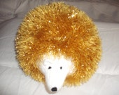 hand knitted tinsel hedgehog in King Cole tinsel wool in gold