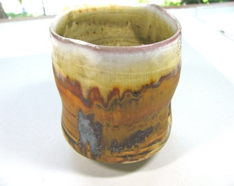 "Ceramic vessel, handmade, wheel thrown, altered, 4 and 1/2"" high and 3 and 1/2"" wide at the top, earthy colors, brown, yellow and white"