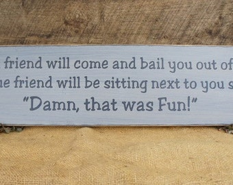A good friend will come and bail you out of jail, but a true friend will be sitting next to you saying, Damn that was fun Comical lol sign.
