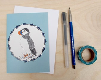 Puffin and herring A6 Digitally printed greetings card. Featuring an illustration of a puffin surrounded by herring.
