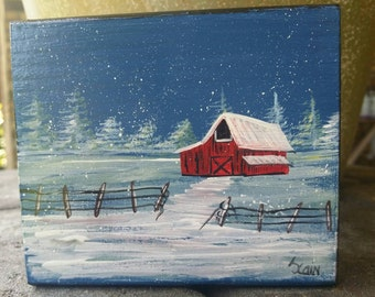 Wood block art  of a a old red barn in the snow