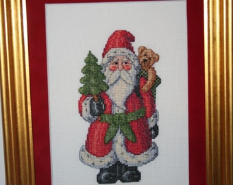 Cross Stitched Print of Santa with a Christmas Tree and a sack with a bear for a gift.