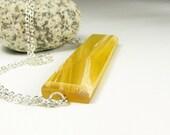 Medium size wood resin fusion pendant.Semi translucent yellow resin on bamboo. All natural UVpoxy.
